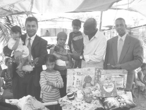 The Mark Benschop (right) Foundation in association with businessmen Peter Ramsaroop (left) and Ron Morrison (second from right) putting smiles on the faces of Michelle Russel and her four children whose father police killed last week.