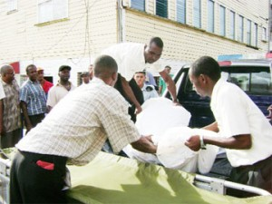 The body of one of the two men shot dead by the police at Goat Farm, Region 10 being loaded on to a stretcher at the Ogle Airport yesterday.