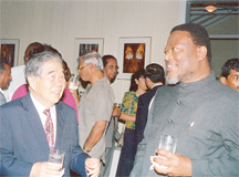Arthur Chung (left) sharing a light moment with Prime Minister Sam Hinds at a Canada Day reception in July 1999. (Stabroek News file photo)