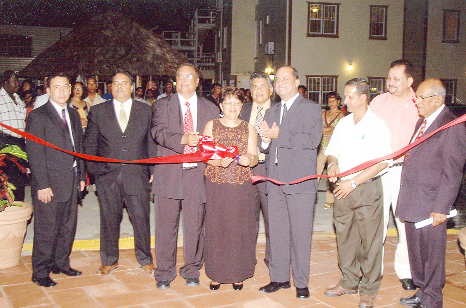 Sita Shewnarain [centre), owner and director of the Aracari Resort cuts the ribbon to officially open the resort last Thursday. Assisting her is her husband, Sase Shewnarain while Minister of Tourism, Industry and Commerce, Manniram Prashad (fourth from right) looks on in the presence of other guests.
