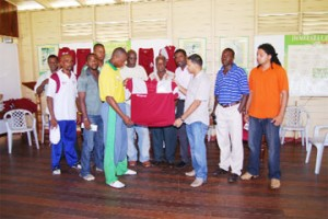 Middle St. Plaza Managing Director Salim Paul hands over the new DCC uniforms to club player Christopher Barnwell in the company of DCC officials (Lawrence Fanfair photo)