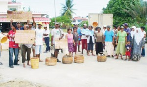 Cotton Tree residents, fed up after having been without potable water for two weeks, protesting on the street yesterday. The residents held placards and used empty buckets and baskets to demonstrate their point. (Photo by Shabna Ullah)
