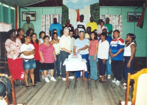 Stabroek News Editor in Chief and Chairman of the Board of Directors David de Caires and his wife Doreen de Caires (centre) cut the cake in the presence of staff at this newspaper's 20th anniversary celebration in November 2006. (Stabroek News file photo)