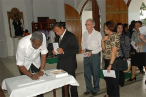 The book of condolence being signed by Hugh Cholmondeley for Stabroek News Editor-in-Chief David de Caires at yesterday's memorial service.
