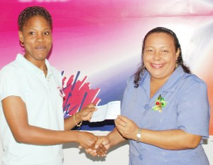 The Guyana Lottery Company on Wednesday handed out prizes to its Instant Ticket Promotion winners. In photo, the 1st prize winner Rowena Seymour (right) receives her $300,000 cheque from Shevaun Brotherson of the lotto office.