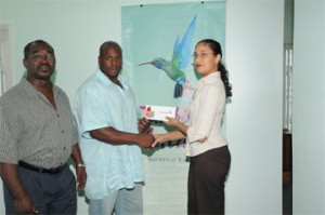 Mr. Guyana Mark Anthony Perry (left) receives his two airline tickets from Caribbean Airlines Sales Executive Kathleen Shuffler-Ten-Pow, whilst GABBFF president Frank Tucker looks on appreciably. (A Clairmonte Marcus photograph)