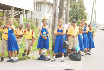 Road safety? Pupils of the West Ruimveldt Primary School stand at a corner near their school awaiting transportation to get home yesterday. A sign that the authorities should address the demarcating of bus stops near schools to prevent this dangerous practice. (Photo by Jules Gibson)