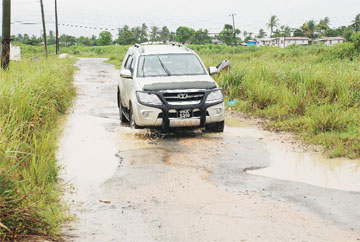 This vehicle tries to manoeuvre around the potholes on the Great Diamond road.