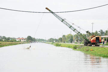 This dragline was cleaning a trench at Greenfield yesterday afternoon. Most of the floodwater has receded from this community.