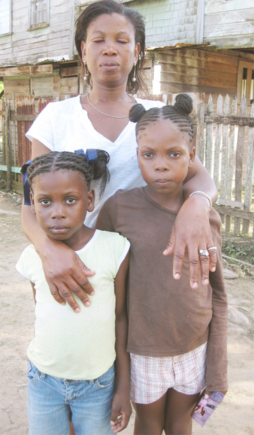 The distraught Erica Johnson with her two other daughters, Tovany (right) and Kiszy.