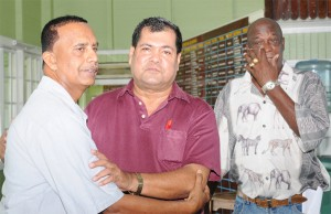 NO HARD FEELINGS! Challenger Bishwa Panday, left,  and Guyana Cricket Board (GCB) president Chetram Singh embrace following the result of yesterday's annual general meeting as former national fast bowler Robert Adonis, right, wipes something (not a tear) from his eye. (Aubrey Crawford photo)