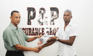Trinidad bound: Travis Blyden receives his bowling boots from P & P Insurance head Bishwa Panday.