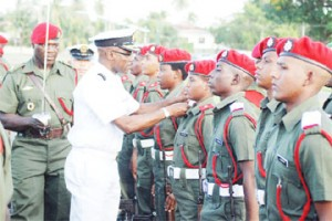 Woman Officer Cadet F Boyce (fourth, right) being decorated with her ensign badge of honour by Chief of Staff of the Guyana Defence Force Commodore Gary Best at the parade yesterday. (Jules Gibson photo)