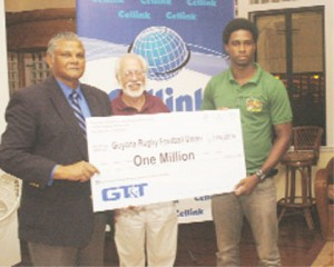 Chief Executive Officer of GT&T, Major General (retired) Joe Singh,  left, presents a sponsorship cheque for $1M to GRFU's West Indies Sevens captain Claudius Butts (right). Kit Nascimento, president of the West Indies Rugby Union, stands at centre. (Aubrey Crawford photo)