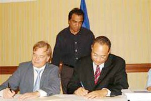 Bernal (right) signing the EPA agreement with Karl Falkenberg, the Deputy Director General for Trade at the European Commission. To the rear, Kusha Haraksingh, lead negotiator on EPA legal issues with the College of Negotiators.
