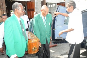 First class umpire Clyde Duncan (second right) and president of the Georgetown Cricket Umpires Council (GCUC) Grantley Culbard (left) lead the pall bearers bearing the body of their former colleague Compton Vyphuis. (Clairmonte Marcus photo)