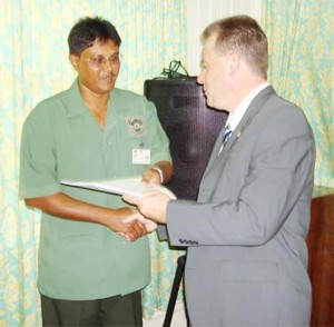 James Singh, Commissioner of Forests (left) receiving a signed copy of the agreement from Dominick Plouvier, Director WWF, Guyana. (Ministry of Agriculture photo)