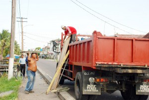 Two men load a truck provided by the Ministry of Public Works with building materials.
