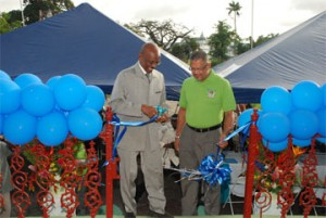 Left in photo is Mayor Hamilton Green as he performs the symbolic cutting of the ribbon in acceptance of the newly refurbished bandstand while Edwin Gooding, Managing Director of Republic Bank looks on.