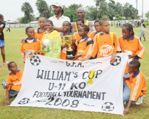 The Fruta Conquerors team poses with the Williams Cup Trophy after defeating Santos 1-0 in the final at Tucville Playfield yesterday. Coach, Kurt Cadogan stands at the back of his players. (Clairmonte Marcus photo)