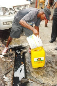 Filling up: This man made the best of the fuel spill yesterday as he dipped from the drain and poured into his jerry can