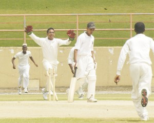 A dejected looking Brian Hussain of Berbice High School (BHS) leaves the field after being bowled by Queen's College's Neil Barry Jnr., (not in picture), as wicketkeeper Avion Rodrigues and other Queen's College teammates celebrate. (An Aubrey Crawford photograph)
