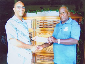Project Manager of H. Nauth and Sons Construction Company, Julian Archer, left, hands over part of the race sponsorship to coach of the club Randolph Roberts.