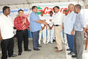 President of the Guyana Cricket Board (GCB) third left, receives the sponsorship cheque from Castrol brand manager Leonard Khan (3rd from right) while from left are Essequibo Cricket Board president Sheik Ahmad, Demerara  Cricket Board president Bissoondial Singh, ECB vice president Faizul Bacchus and David Blacks along with some East Coast players looking on appreciatively. (A Clairmonte Marcus photograph)