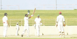 Watched by from left Justin Guillen, Devendra Bishoo and wicketkeeper Gibran Mohammed, Guyana's Narsingh Deonarine (2nd left) soaks up the applause from his teammates after posting his fifth first class ton yesterday. (An Aubrey Crawford photograph)