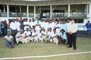 The victorious Lusignan Cricket Club (LCC) 'A' team and their supporters strike a pose with president of the Demerara Cricket Board and acting president of the Guyana Cricket Board Bissoondial Singh (right). (Clairmonte Marcus photograph)