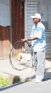 Picking up loose ends: This GPL employee was rolling up a section of the cable removed from a house yesterday, which had abandoned its metered connection to use an illegal one. (Photo by Jules Gibson)
