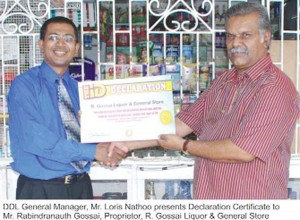 DDL General Manager Loris Nathoo (left) presents the Declaration Certificate to Rabindranauth Gossai, proprietor of R Gossai Liquor and General Store.