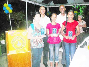 Rotary Club of Stabroek Peace Poster winners Serena Ming, Divya Lall and Zimeena Rasheed display their plaques at a ceremony held to honour them while Club members look on.