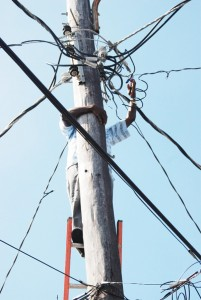 An employee of the Guyana Power and Light Company (GPL) snapping an illegal connection on a lamppost in Albouystown yesterday. (Photo by Jules Gibson)