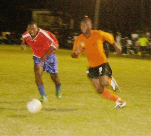 Mayor's Cup Action.  This Camptown forward at right is seen going on the attack against Pouderoyen as a defender tries to keep up with him in the final first round match of the Mayor's Cup Competition at the GFC ground. (An Orlando Charles photo)