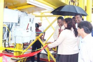 Prime Minister Samuel Hinds (left) cuts the ribbon to officially open the operations of the Guyana Sand Port company.