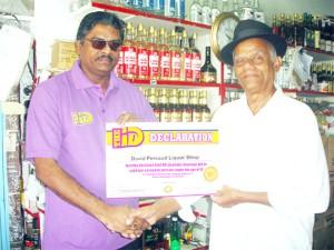 DDL representative Hargobin Hariram (left) presents the ID Declaration Certificate to the proprietor of the David Persaud Liquor Shop Durgo Persaud.