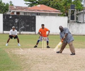 Commissioner of Police, Henry Greene, plays a drive to get the action rolling in the Leo Club seven-a-side tapeball tournament held at the DCC ground on Tuesday. (Clairmonte Marcus Photo)