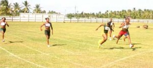 Tiffany Carto (2nd from R) crosses the finish line first ahead of Ruralites Deja Smart (3rd from L) and fellow club mate Maliyka Francois (R) in the National Youth/Junior championship yesterday at the Enmore Sports Club ground. (Orlando Charles Photo)