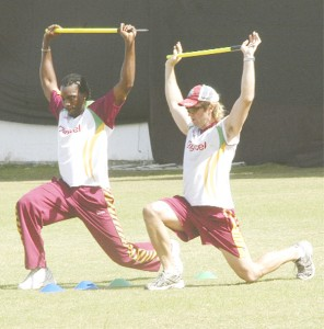 West Indies skipper Christopher Gayle (left) shows no signs of discomfort when he was caught doing some light stretches with team physiotherapist CJ Clark.