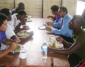 Minister of Sports Dr. Frank Anthony having lunch with the Alpha United football Club yesterday at Camp Soweyo (Rawle Toney photo)