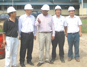 Minister of Agriculture, Robert Persaud (centre) speaking to the Vice President of CNTIC, Zhang Guodong while site representative Andrew Jin (right) and other Chinese officials look on.