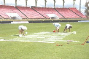 In these two Aubrey Crawford photographs, at left Wasim Habib can be seen rolling the pitch that will be in use for tomorrow's game, while at right workmen were caught painting the sponsor's logo to the side of the pitches.