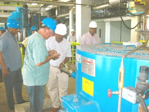 General Manager, Technical Services, Yusuf Abdul (third from left) and Shadow Agriculture Minister, Anthony Vieira (second from left) examine the sugar.