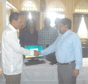 Finance Minister Dr Ashni Singh (right) and Deputy Mayor Robert Williams shake hands on the computer deal.