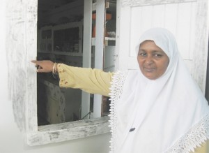 Ameena pointing to fingerprints on the window that the men broke to enter the building.