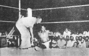 Calvin Garraway sits dazed on the canvas as referee Wheating gives him the count.