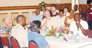 Sir Vivian Richards (with microphone) regales the audience at the Le Meridien Pegasus Hotel Thursday night about his exploits with the West Indies team. Other in picture around the head table are from left, Fazeer Mohammed, Roger Harper, Reds Perreira and Tony Cozier. (Orlando Charles photo)