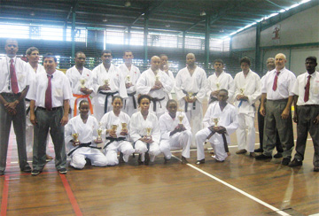 The karatekas take time out after competing to pose with the judges who are Marvin Singh (left) and Christopher Chaves (second left), Nandra Lall (right) Amir Khouri (second right) and Winston Dunbar (partly hidden behind Khouri).