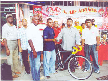 Managing Director of A. Ally and Sons Limited Faizal Ally (second right), presents the track cycle to Neil Reece Jnr. (second left) while store supervisor Zahir Khan, Banks DIH Berbice branch manager Reginald Matthews (centre) and other store personnel  and FACC members look on.